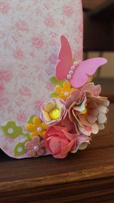 Nome  Lívia em MDF decorado com a  técnica de scrapdecor, letras  foradas com  papéis de scrapboook, flores feitas  a partir de  furadores. Menina  com  flores comprada  no site da silhuette Design. Borboleta com flores.