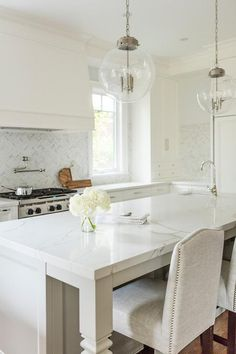 Instead of marble, a quartz countertop gives the appearance of solid marble delivering a lovely white and gray lustrous shine across a white kitchen island with carved legs.