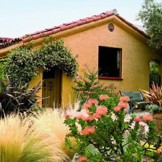 Unthirsty easy-care plants, including Mexican feather grass, blue hibiscus, New Zealand flax, and orange pincushion create drama while star jasmine frames the gate of this Spanish colonial rivival home.