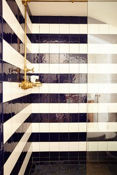 Black and white tiles form a striped pattern on the shower wall of a room at The Crow's Nest Inn, Montauk, NY...