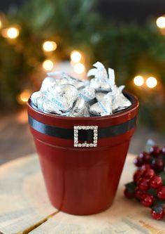 Here's a fun DIY gift for your neighbors this Christmas season-a cute Elf and Santa candy pot that is filled with candy. Grab a flower pot and paint and decorate it, then fill it with candy and it's a great gift!