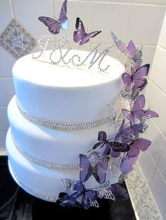 Purple Butterfly Bling Wedding Cake - This is my latest cake for a beautiful friends wedding. She LOVES Butterflies, the colour purple and anything shiny or bling!  We have two layers of 2 layer diamante chain around the bottom of each tier. The butterflies were bought off Ebay, they are hand cut butterflies printed on clear plastic. I glued each one onto wire so I could put them on the cake better.  The cake is set off with the couples initials in bling letters!! :)