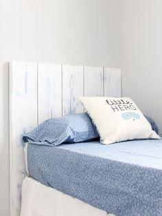 Cama vestida en azul y blanco con cabecero de lamas