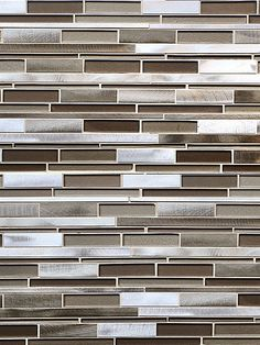 Brown glass tiles mixed with brown metals and gray metal tiles to create subway mosaic backsplash tile.