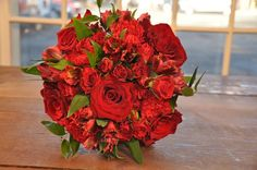 Red Passion Bridal Bouquet - A stunning, rich wedding bouquet of deep red roses, spray roses, dianthus and alstromeria, interspersed with lush green ruscus.  Finished with your choice of double-faced satin or burlap and lace and pins.