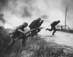 """Soldiers of 2. SS-Panzer-Division """"Das Reich"""" running across the road of a burning Soviet village in 1941."""