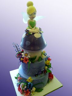 A tinkerbell Cake - 3 tiers  tinkerbell cake, buttercream bottom 2 tiers, and fondant (mushroom) top 2 tiers.    gumpaste flowers and tinkerbell figurine