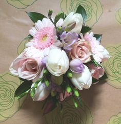 Pretty bridesmaids hand-tied with roses, gerbera, freesias and tulips.