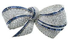 "Brooch set with 173 round brilliant cut diamonds from 0.03 to 0.05 cts., estimated combined diamond weight 7.16 cts., color F-G, clarity VVS-VS, 104 square faceted sapphires from 0.03 to 0.07 cts., estimated combined sapphire weight 3.12 cts., cast and assembled 18 kt. white gold mount marked ""750"", ""18 Kt."", ""*1952AL"", 60 x 32 mm., 27.2 grams gross weight"