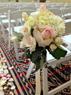 This bride's color palette were whites, creams and light pinks. We used the white hydrangea, the pale pink rose & spray rose from her floral palette to pull together the aisle markers she wanted.