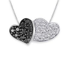 The remarkable sweetness of this pendant necklace is both a tribute and a reminder of a love shared by two. The exquisite design features a double heart adorned in brilliant black and white diamonds.