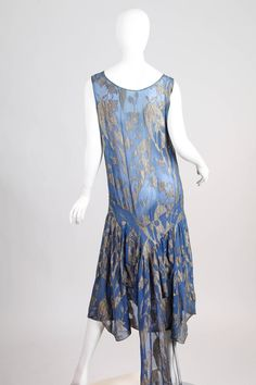 1920s Evening dress Blue silk chiffon with woven silver Lamé floral motifs. Cut with a low neckline which would have been worn over a lace trimmed slip. The dress has a small train that has snaps on its ends to tuck it up inside when not wanted. Morphew Back 4