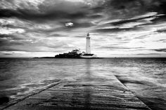 Black and white landscape photography: coastal view across the water looking towards a lighthouse