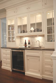 wet bar by Kitchen Design Diary. Love the white cabinets with the glass doors. Classy!