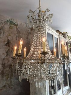 love the juxtaposition of the crystal chandelier against the worn plaster walls. Stunning!