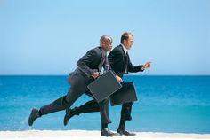 Businessmen running on a beach.