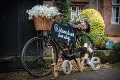 Vintage bicycle set up with LOVE letter, co-ordinating tin cans, fresh flowers and seasonal plants, welcoming guests to a wedding xx