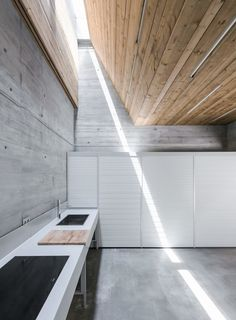 A ribbon of light ties a concrete kitchen to its picturesque landscape.