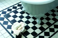 Here black and white geometric tiles have been used to highlight the area around the freestanding bath in this traditional bathroom.
