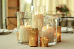 Centerpiece Inspiration: Cluster of pillar candles in cylinder vases, skinny cylinder vases with floating candles, and gold ribbed mercury glass votives  www.stemfloral.com