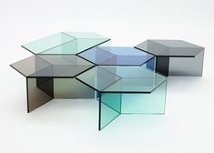 Sebastian Scherer has created a series of tables called Isom. The tables are made completely in 10mm sheets of blue, green, grey, and bronze glass, each with a hexagon-shaped top. Supported by three pieces of rectangular glass vertical panels, the tops appear to form rhombuses when looking down at them because of the edges of the base pieces.