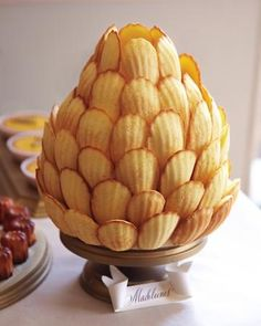 Arranged in the shape of a pineapple (a symbol of friendship), this madeleine structure was made by covering a foam form in rolled fondant and then, starting from the bottom, attaching the cookies to it with thin wooden skewers. weddings-food-drink