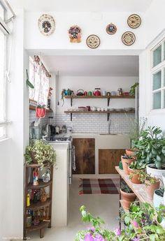 Cozinha tem piso de cimento queimado, subway tiles e móveis de madeira de demolição.