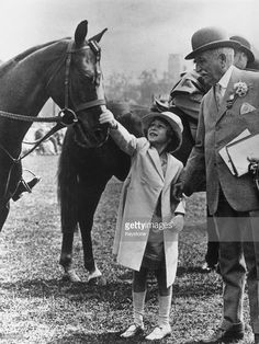 Princess Elizabeth, later Queen Elizabeth II, reaches up to pat the head of a horse at the Richmond Royal Horse Show on 6th June 1934.