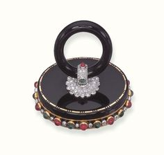 A DELICATE ART DECO ENAMEL AND MULTI-GEM PILL BOX, BY CARTIER  Designed as an oval black enamel case with onyx ring, the top enhanced by a pavé-set diamond rosette with cabochon ruby and emerald detail, geometric trim and an alternating cabochon ruby and emerald border with collet-set diamond spacers to the ruby push-piece opening to reveal a covered compartment, circa 1930