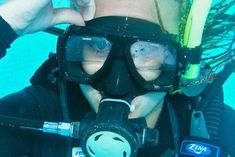 A scuba diver breathes past the water in her scuba mask.