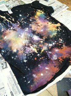 DIY Galaxy Shirt:: Black shirt (or shoes, hat, etc), Spray bottle, Bleach, newspaper, White acrylic paints +  Blue + yellow + purple + silver Fabric Paint (or any colors you want.)