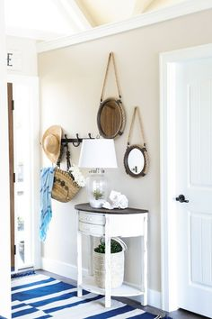 Cottage foyer features round rope mirrors mounted on beige walls over whitewashed half moon console table with contrasting black top topped with clear glass lamp filled with sand atop white and blue striped rug.