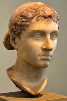 "The ""Berlin Cleopatra"" is likely of Italian provenance and may have been made when Cleopatra was in Rome. Or the bust may have been the work of an Alexandrian sculptor and brought with her. She wears the royal diadem, a broad ribbon of cloth tied around the hair that first had been worn by Alexander the Great and came to symbolize Hellenistic kingship. Small ringlets frame the brow, curls that are less visible on the Vatican bust."