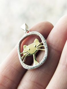 Cat necklace: Brass kitty within a framework of sterling silver. Handmade by artisans in El Alto, Bolivia. $14.99