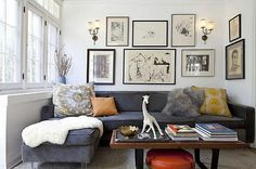 art wall, grey couch & cushions, ottoman under the table.  Rug on couch.