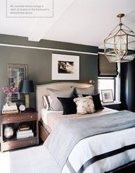 bedroom with deep charcoal walls and white molding accent near ceiling