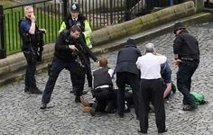 A policeman points a gun at a man on the floor as emergency services attend the scene outside the Pa... - PA Wire/PA Images