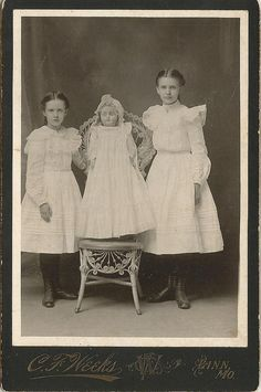 Two sisters posed next to a large doll propped in a wicker chair