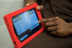 Inmate holds a prison tablet showing email