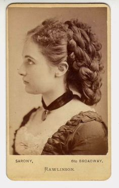 1870s Look: frizzy bangs, real hair pulled back & hidden with loads of looped false braids. Add a wide ribbon w/charm to complete the style. :-)