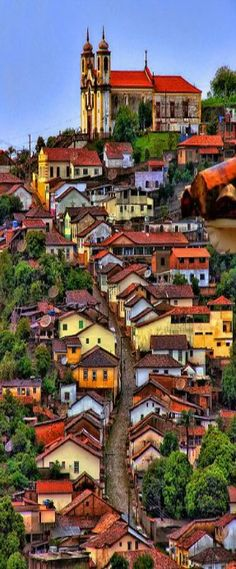 The hillside is covered in bright homes in Minas Gerais, Brazil.- Little Passports #littlepassports #minasgerais #brazil