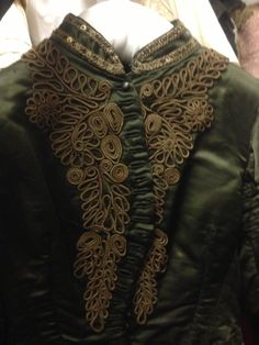 Stand up collar, unusual embroidery detailing on the front panels with diagonal button fastenings