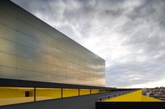 Theatre and Auditorium Poitiers by JLCG Arquitectos via Architizer. Note the reflection of the clouds in the translucent glass facade with a bleed of color coming from behind. #Color #Glass.