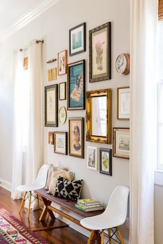 Antique and vintage touches make this hallway gallery wall a true gem. Eames chairs and an entryway bench add more.