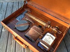 Survival Kit for Gentleman - The kit features everything you would need in an emergency including a flask, whiskey, hatchet, matches, and a handful of other goods packed into a vintage briefcase.