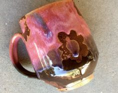 Mug in stock and ready to ship.   Each mug hand thrown, and glazed individually! See all photos for the usual variations of these mugs glaze and design. Handmade stoneware pottery coffee mug glazed in bright coral/tangerine and deep cranberry red with a loose swirly design.  ***Each mug design varies a bit, but all are very similar to photo--holds approx 14-16 oz approx 4 tall and 3.25 wide. convo me with questions.  These are stock photos--your mug will not be the exact one pictured but...