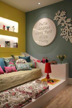 décoration chambre adulte en bleu pétrole et jaune moutarde, lit monté sur plate forme, avec des coussins colorés aux motifs fleuris, sol recouvert de revêtement imitation bois en couleur marron clair