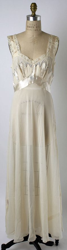 "Embroidered silk chiffon nightgown with satin and crepe detailing and lace trim, by Reginé Brenner, American, 1952. The owner's name, ""Diane"", is embroidered at center front of the satin waistband, in the same pale blue thread as the rest of the embroidery. Label: ""Lingerie/Reginé Brenner/New York"""