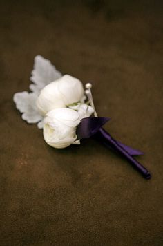 The groom's boutonniere is made of white ranunculus, dusty miller and wrapped in purple ribbon.