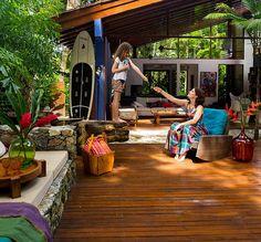 Nesta área externa com deque de madeira, o uso de tecidos, plantas e vasos coloridos deixam o visual muito mais divertido. O clima fica perfeito para curtir os dias ao ar livre. Projeto da arquiteta Fabiana Avanzi